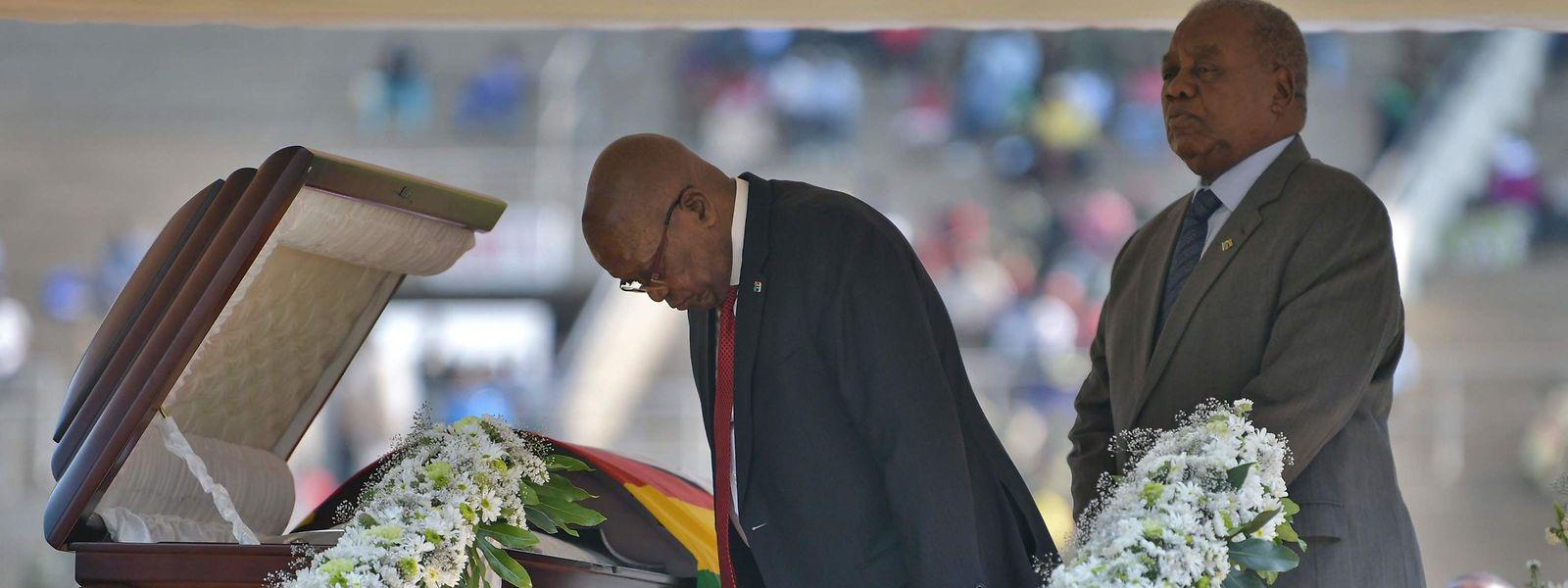 Der frühere Präsident Südafrikas, Jacob Zuma (l.) am offenen Sarg von Robert Mugabe.