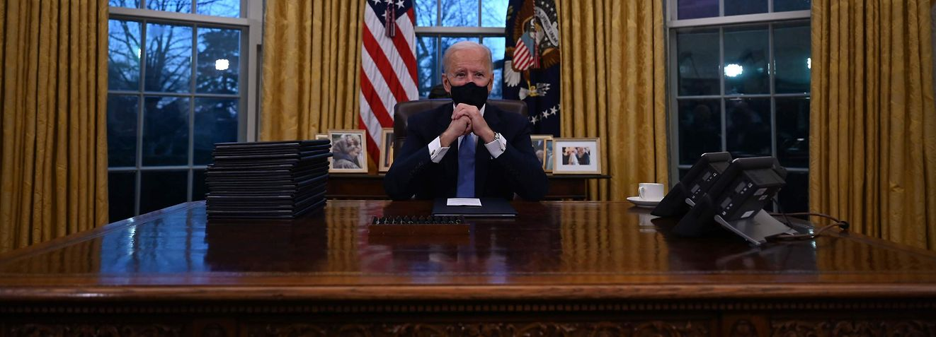 TOPSHOT - US President Joe Biden sits in the Oval Office at the White House in Washington, DC, after being sworn in at the US Capitol on January 20, 2021. - US President Joe Biden signed a raft of executive orders to launch his administration, including a decision to rejoin the Paris climate accord. The orders were aimed at reversing decisions by his predecessor, reversing the process of leaving the World Health Organization, ending the ban on entries from mostly Muslim-majority countries, bolstering environmental protections and strengthening the fight against Covid-19. (Photo by Jim WATSON / AFP)