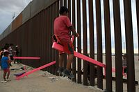 """(FILES) In this file photo taken on July 28, 2019 American and Mexican families play with a toy called """"up and down"""" (seesaw swing) over the Mexican border with US at the Anapra zone in Ciudad Juarez, Chihuahua State, Mexico. - Two California professors have installed seesaws across the US-Mexico border in a blunt rebuke to President Donald Trump over his plans to build a wall along the 2,000-mile boundary between the two countries.The three pink seesaws were unveiled on July 29, 2019 at a border fence separating Sunland Park, in New Mexico, and Ciudad Juarez, in Mexico, allowing kids and adults on either side to play together. (Photo by LUIS TORRES / AFP)"""