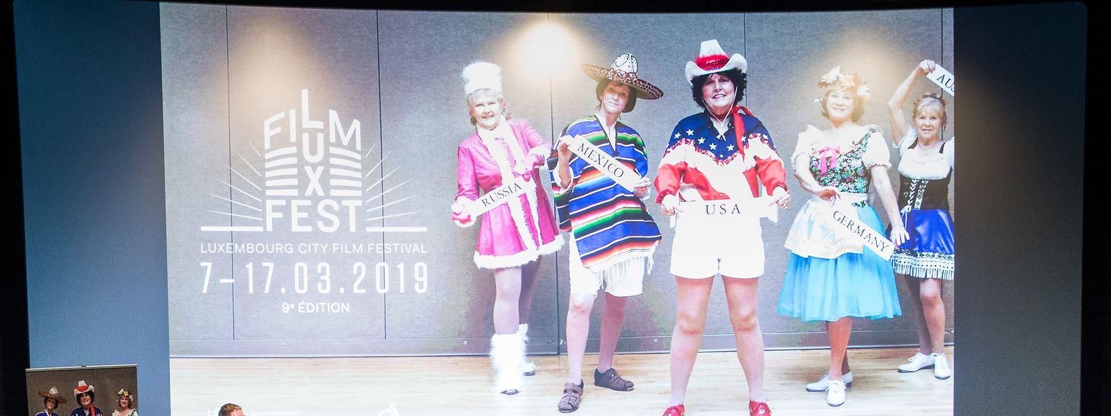 """Pressekonferenz vor dem offiziellen Festivalplakat, das Humor und Farbe vereint – mit Senioren einer Rentnersiedlung aus Arizona, die als Stepptanzgruppe die Länder der Welt repräsentieren: Das Bild ist der """"Sun City""""-Reihe der Fotografin Marion Gambin entnommen."""