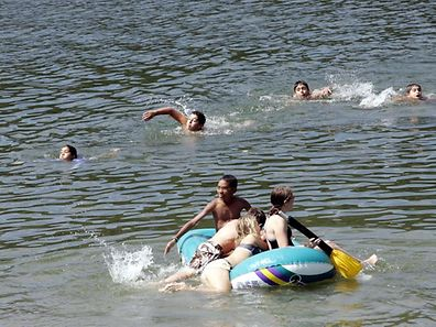 Children and young people splash in the water of the manmade Upper Sûre lake in Insenborn, northern Luxembourg