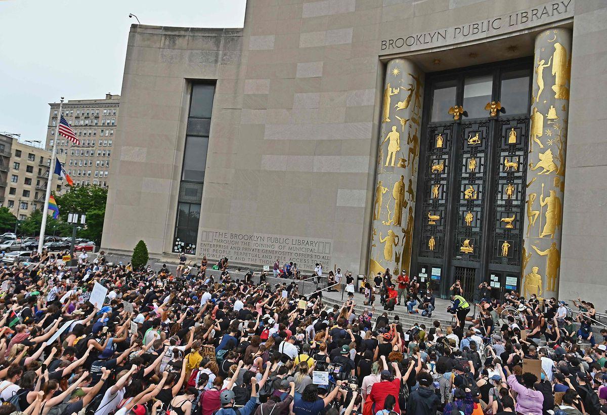 New York: Demonstranten gehen auf die Knie und heben ihre Faust.