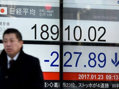 A businessman walks past an electric quotation board flashing the Nikkei key index of the Tokyo Stock Exchange.