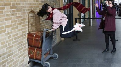 """A Harry Potter fan poses for a photograph during a visit to Platform Nine and Three-Quarters at Kings Cross station in London, Britain, March 21, 2017. REUTERS/Neil Hall  SEARCH """"HALL POTTER"""" FOR THIS STORY. SEARCH """"WIDER IMAGE"""" FOR ALL STORIES."""