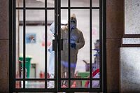 This photo taken on March 1, 2020 shows a medical staff member looking on through a gate after all patients were discharged at a makeshift hospital set up in a sports stadium in Wuhan in China's central Hubei province. - The number of deaths globally in the new coronavirus outbreak passed 3,000 on March 2, as China reported more 42 deaths. (Photo by STR / AFP) / China OUT