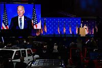 """Supporters of Democratic presidential nominee Joe Biden listen to him speak, next to his wife Jill Biden, during election night at the Chase Center in Wilmington, Delaware, early on November 4, 2020. - Democrat Joe Biden said early Wednesday he believes he is """"on track"""" to defeating US President Donald Trump, and called for Americans to have patience with vote-counting as several swing states remain up in the air. """"We believe we are on track to win this election,"""" Biden told supporters in nationally broadcast remarks delivered in his home city of Wilmington, Delaware, adding: """"It ain't over until every vote is counted."""" (Photo by ANGELA WEISS / AFP)"""