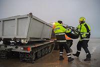 """08.01.2019, Niedersachsen, Borkum: Dirk Baake (l) und Timo Paechnatz, Einsatzkräfte des Havariekommandos, haben am Strand von Borkum einen Autoreifen gefunden, den sie zu dem schwimmfähigen Mehrzweckfahrzeug """"Hägglunds"""" tragen. Auf Borkum wurde die Suche nach angespülter Ladung fortgesetzt, die der Frachter «MSC Zoe» vorige Woche auf dem Weg nach Bremerhaven verloren hatte. Foto: Mohssen Assanimoghaddam/dpa +++ dpa-Bildfunk +++"""