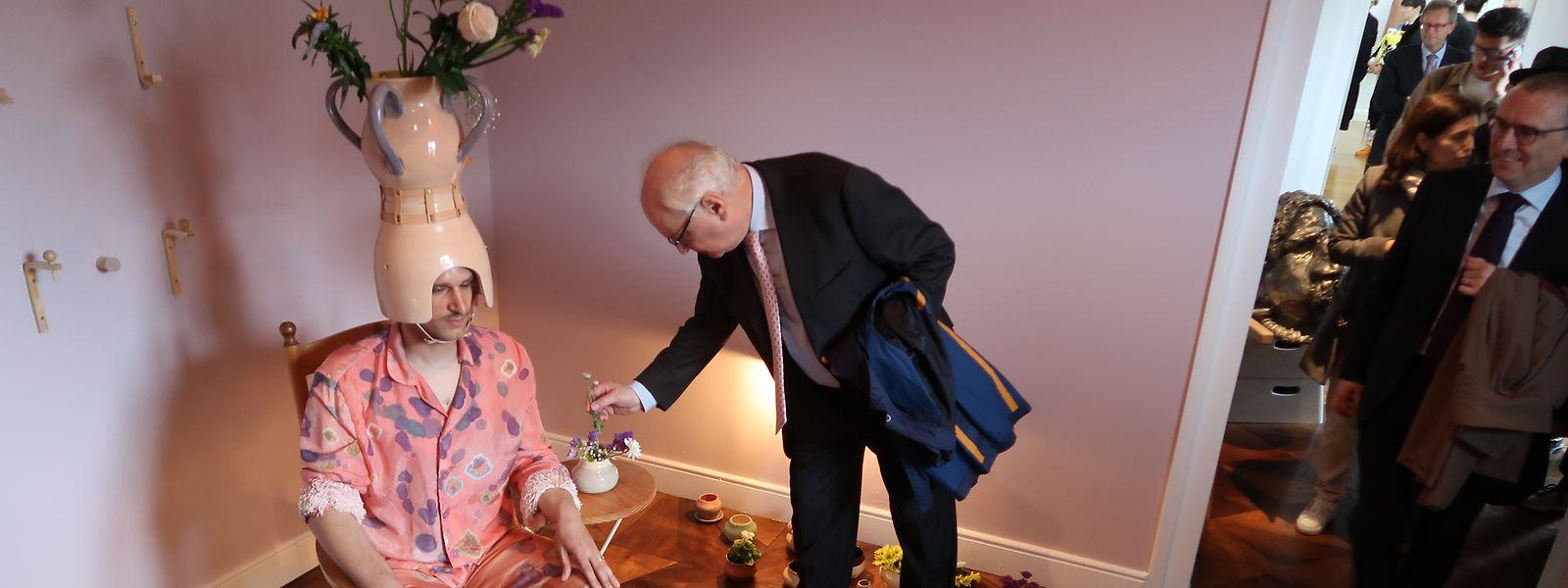 """""""Thank you so much"""": In seinem Kostüm bedankt sich Mike Bourscheid für die Blumen, die ihm die Eröffnungsbesucher in die Künstlerwohnstube bringen  - und diese unter anderem in der Vase auf dem Kopf platzieren."""