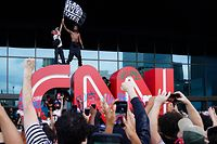 ATLANTA, GA - MAY 29: A man waves a Black Lives Matter flag atop the CNN logo during a protest in response to the police killing of George Floyd outside the CNN Center on May 29, 2020 in Atlanta, Georgia. Demonstrations are being held across the U.S. after George Floyd died in police custody on May 25th in Minneapolis, Minnesota.   Elijah Nouvelage/Getty Images/AFP == FOR NEWSPAPERS, INTERNET, TELCOS & TELEVISION USE ONLY ==