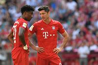 """(FILES) In this file photo taken on August 31, 2019 Bayern Munich's Austrian defender David Alaba (L) and Bayern Munich's Polish striker Robert Lewandowski (R) talk during the German first division Bundesliga football match FC Bayern Munich versus Mainz 05 in Munich. - Bayern Munich are unlikely to release stars Robert Lewandowski and David Alaba for forthcoming World Cup qualifiers in the UK due to the British variant of the Covid-19 virus. """"We are not taking any risks. We want to have the players back in training and match rhythm straight away. That's what the decision will depend on,"""" Bayern coach Hansi Flick said on March 16, 2021. (Photo by Christof STACHE / AFP) / RESTRICTIONS: DFL REGULATIONS PROHIBIT ANY USE OF PHOTOGRAPHS AS IMAGE SEQUENCES AND/OR QUASI-VIDEO"""