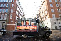 """27.11.2019, Großbritannien, London: Einer von vier Kleinlastern mit Plakaten der Liberaldemokraten, die in den Bezirken Werbung betreiben, in denen die Sitzverteilung zwischen Liberaldemokraten und Konservativen noch schwankt, fährt kurz nach der Enthüllung des Plakats mit der Aufschrift """"Brexit is good for them. How is it for you? Stop Boris. Stop Brexit."""" (""""Brexit ist gut für sie. Wie ist es für dich? Stopp Boris. Stopp Brexit."""") und den lachenden Gesichtern von Farage (l-r), Johnson und Trump und am Smith Square. Am 12. Dezember 2019 finden in Großbritannien Neuwahlen statt. Foto: Aaron Chown/PA Wire/dpa +++ dpa-Bildfunk +++"""