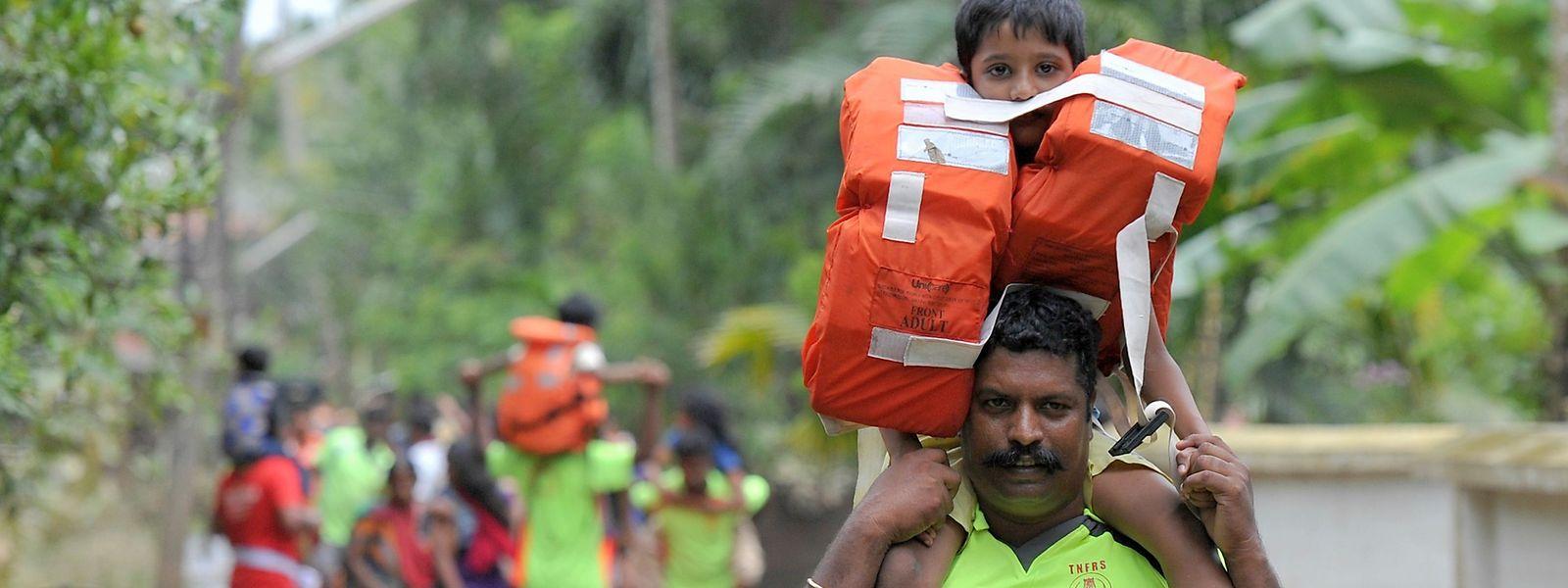 Feuerwehrleute tragen Kinder mit Schwimmwesten aus dem überfluteten Dorf Annamanada.