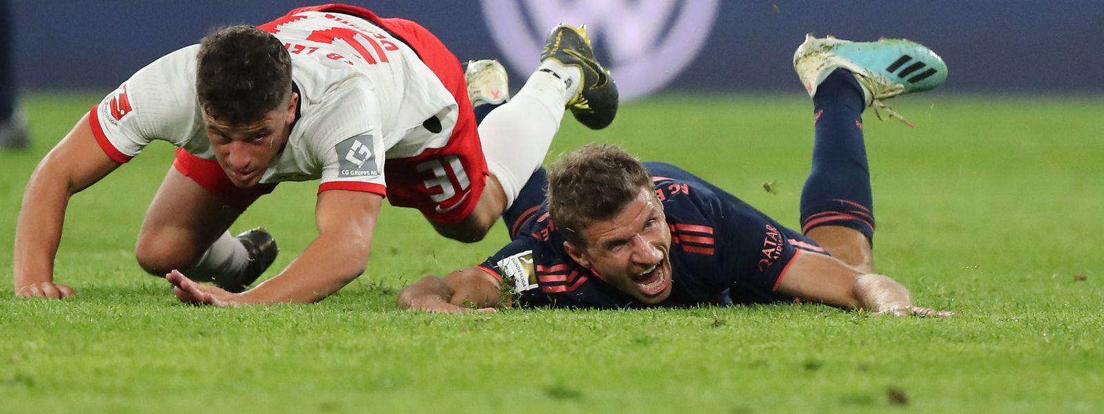 Leipzigs Diego Demme und Thomas Müller (r.) vom FC Bayern gehen zu Boden.