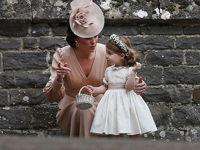 Britain's Catherine, Duchess of Cambridge (L) speaks to her daughter Britain's princess Charlotte, a bridesmaid, following the wedding of her sister Pippa Middleton to James Matthews at St Mark's Church in Englefield, west of London, on May 20, 2017. After turning heads at her sister Kate's wedding to Prince William, Pippa Middleton graduated from bridesmaid to bride on Saturday at a star-studded wedding in an English country church. The 33-year-old married financier James Matthews, 41, at a ceremony attended by the royal couple and tennis star Roger Federer, wearing a couture dress by British designer Giles Deacon.  / AFP PHOTO / POOL / KIRSTY WIGGLESWORTH