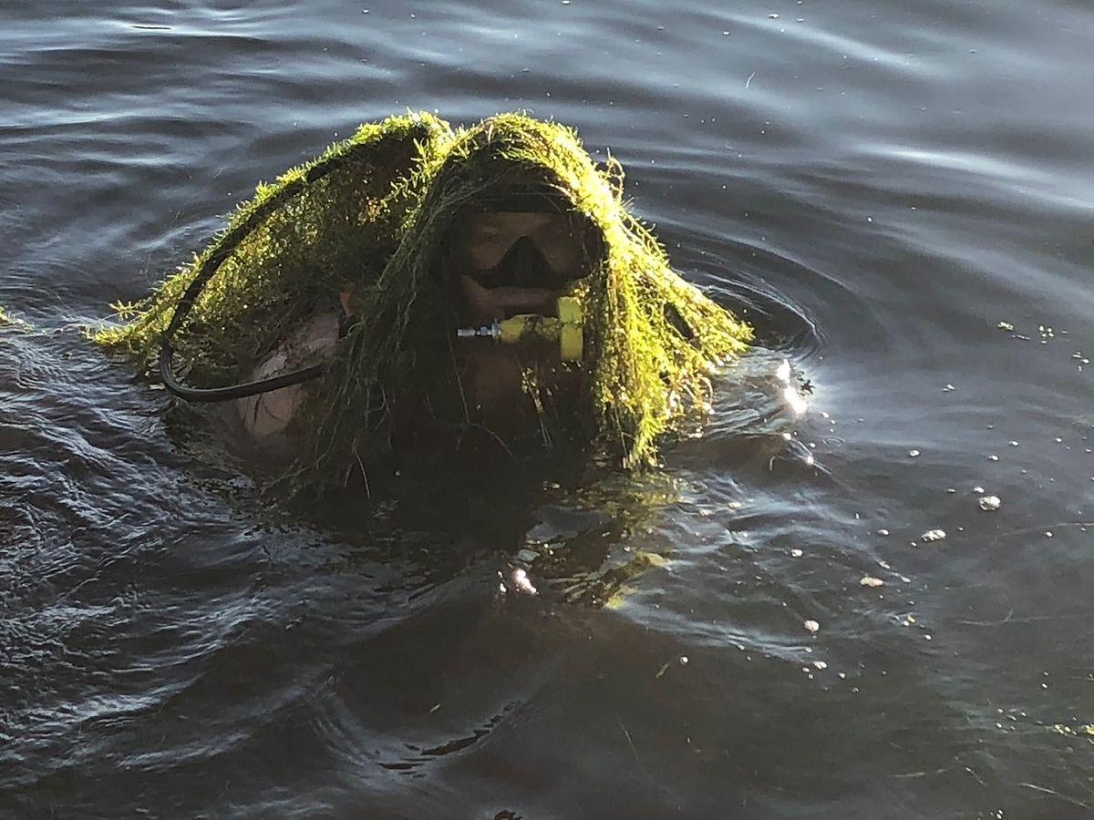 """Um dos mergulhadores do Corpo Grão-Ducal de Incêndio e Segurança, coberto de """"wasserpest"""", a planta que infesta o lago."""