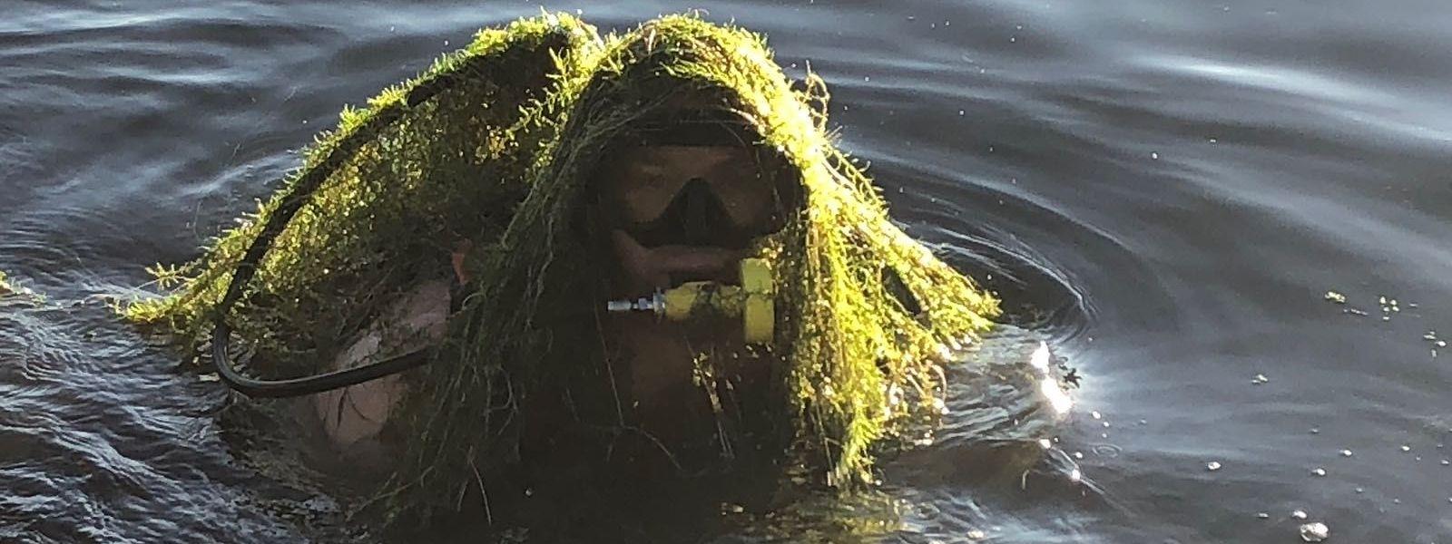 """Um dos mergulhadores do Corpo Grão-Ducal de Incêndio e Segurança, coberto de """"wasserpest"""", a planta que infesta o lago de Remerschen. A foto foi tirada em 29 de julho, durante o resgate do corpo de um búlgaro de 53 anos do lago onde um mês antes morreu o rapper português Puto G."""