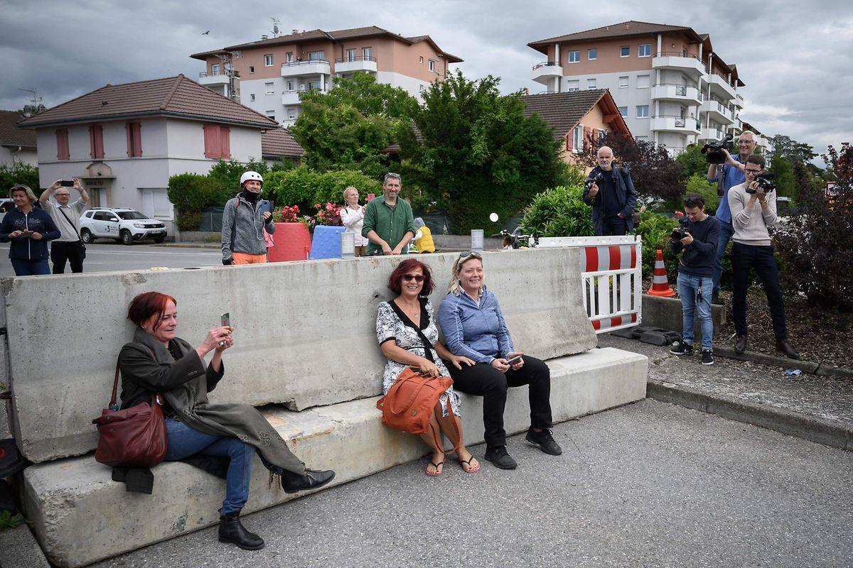 In Thonex an der französisch-schweizerischen Grenze sitzen Menschen auf den zu Corona-Zeiten dort angebrachten Grenzbarrieren, die nun wieder abgebaut werden.