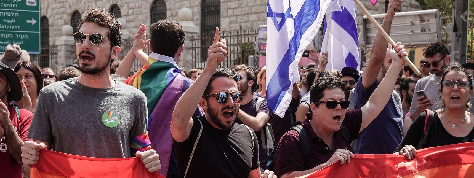 22.07.2018, Israel, Jerusalem: Mitglieder und Unterstützer der Gemeinschaft Lesbian, Gay, Bisexual und Transgender (LGBT) tragen die LGBT-Regenbogenfahne sowie die israelische Flagge und rufen Parolen. Der Protest richtet sich gegen einen letzte Woche verabschiedeten Gesetzentwurf, der es mehr Menschen ermöglicht, eine Leihmutterschaft inAnspruch zu nehmen, homosexuellen Paaren diese Möglichkeit jedoch verwehrt. Foto: Nir Alon/ZUMA Wire/dpa +++ dpa-Bildfunk +++