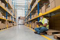 Man working at a distribution warehouse wearing a facemask to avoid COVID-19 and sitting on the floor while doing the inventory – Pandemic concepts