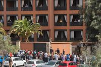 A psychologist talks to a group of workers outside the H10 Costa Adeje Palace Hotel in La Caleta, on February 25, 2020, where hundreds of people were confined after an Italian tourist was hospitalised with a suspected case of coronavirus. - Tourists staying in a four-star hotel on the Spanish island of Tenerife, in the Canary archipielago, were confined to their rooms today following the announcement of a suspected novel coronavirus, COVID-19, case waiting for official confirmation. This possible case was detected yesterday in Tenerife, where an Italian national passed a first test which turned out to be positive, announced the Spanish Ministry of Health. (Photo by DESIREE MARTIN / AFP)