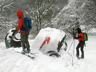 Members of Lazio's Alpine and Speleological Rescue Team are seen next to cars covered in snow in front of the Hotel Rigopiano in Farindola, central Italy