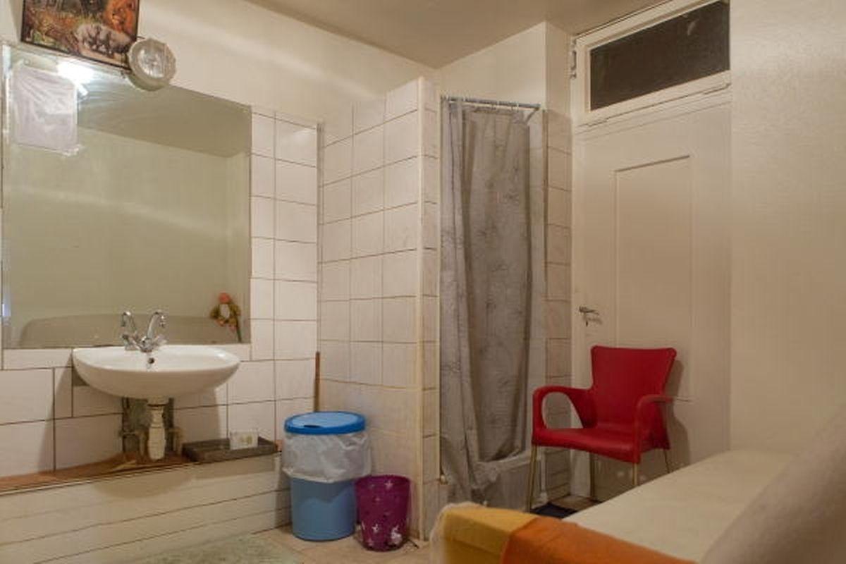 Esta é uma das duas casas-de-banho do café de Nádia. Cada casa de banho tem um duche e um lavatório. A lei diz que são necessários um lavatório para cada dois ocupantes e um duche para cada seis inquilinos.