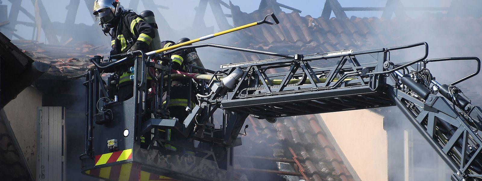 Feuerwehrkräfte im Löscheinsatz: Der Brand in dem Gebäudekomplex nördlich von Straßburg wurde offenbar gelegt.
