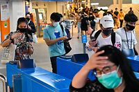 People wearing face masks amidst concerns over the spread of COVID-19 novel coronavirus enter a commuter train station in Bangkok on September 2, 2020. - Thailand on September 2 registered its 100th consecutive day without a local infection of the COVID-19 novel coronavirus, according to an announcement on the kingdom�s Facebook page. (Photo by Romeo GACAD / AFP)