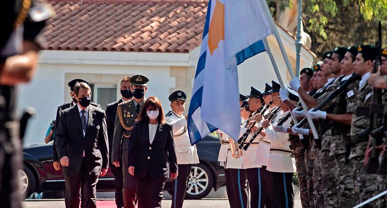 Cyprus' President Nicos Anastasiades (L) and Greece's President Katerina Sakellaropoulou (2nd-L) inspect an honour guard during a welcome ceremony for the latter at the presidential palace in the capital Nicosia on September 21, 2020. (Photo by Iakovos Hatzistavrou / AFP)