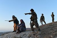 This photograph taken on July 14, 2021 shows Salima Mazari (2nd L), a female district governor in male-dominated Afghanistan, looking on from a hill while accompanied by security personnel near the frontlines against the Taliban at Charkint district in Balkh province. - Mazari, a female district governor in male-dominated Afghanistan, is on a mission -- recruiting menfolk to fight the Taliban. (Photo by FARSHAD USYAN / AFP) / TO GO WITH AFP STORY AFGHANISTAN-CONFLICT-GOVERNOR,FOCUS BY FARSHAD USYAN