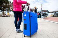 10.05.2021, Niedersachsen, Norderney: Eine Touristin steht nach Ankunft der Fähre mit ihrem Koffer an einer Bushaltestelle am Fährhafen der Insel. Hotels, Ferienwohnungen und andere Quartiere in niedersächsischen Regionen mit einer Sieben-Tage-Inzidenz unter 100 dürfen wieder Gäste empfangen. Buchen können zunächst nur Menschen aus Niedersachsen. Foto: Hauke-Christian Dittrich/dpa +++ dpa-Bildfunk +++