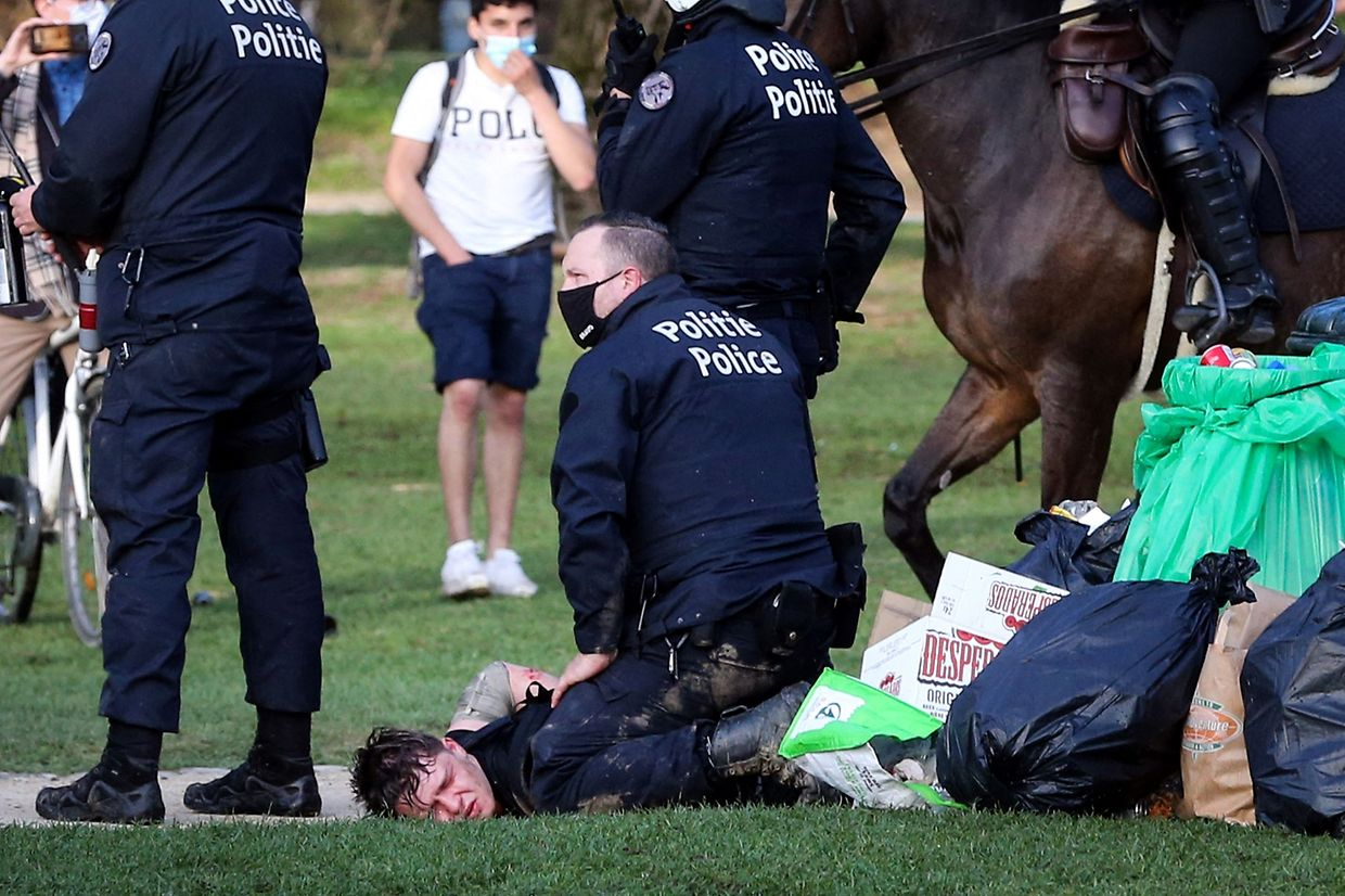 A Belgian police officer arrest a demonstrator at the Bois de la Cambre parc, in Brussels, on April 1, 2021 during a unauthorised rally, for a fake concert announced on social media as an April Fool's Day prank. - Police on horseback and using a water cannon charged a crowd of thousands of people gathered in a Brussels park for a fake concert announced on social media as an April Fool's Day prank. AFP journalists at the scene saw at least one police officer injured and several people in the crowd arrested. (Photo by Fran�ois WALSCHAERTS / AFP)