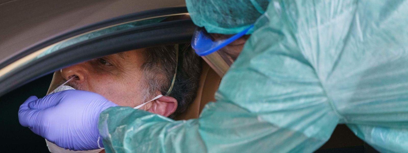 Bei einem Autofahrer wird in einer mobilen Teststation in Burgos eine Corona-Probe durchgeführt.