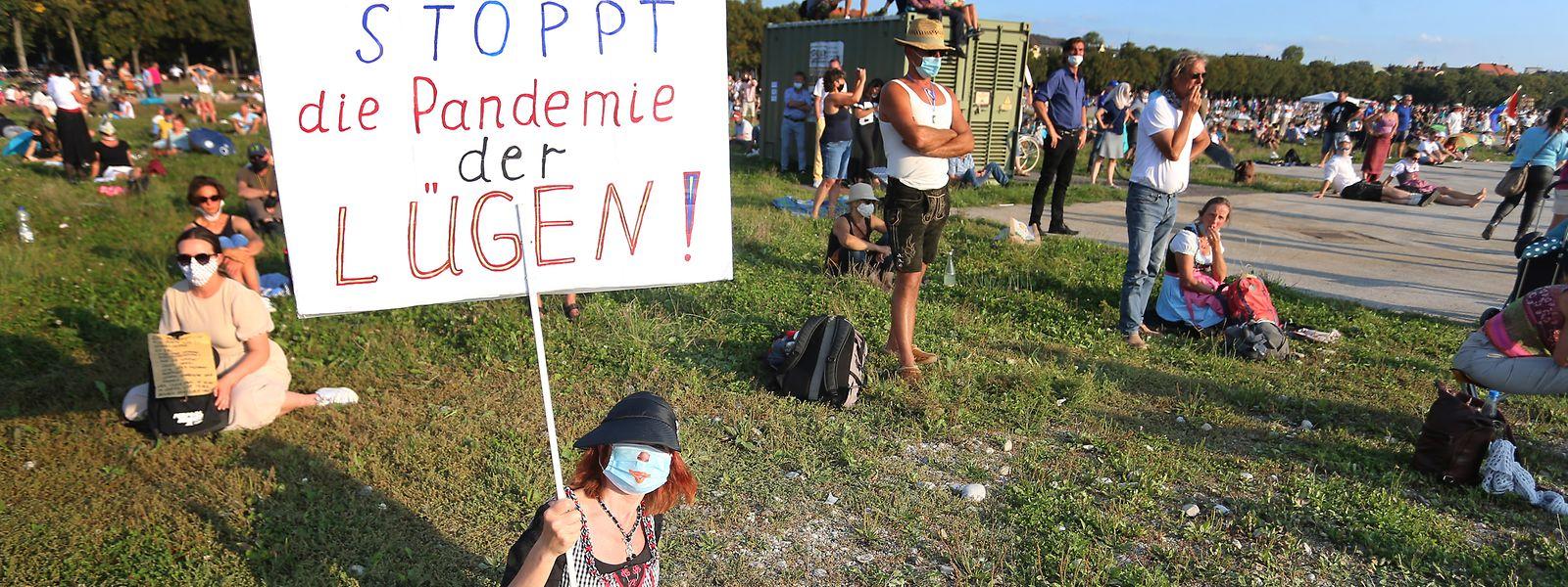 """Eine Frau demonstriert am Samstag auf der Theresienwiese in München mit einem Plakat mit der Aufschrift """"Stoppt die Pandemie der Lügen"""" gegen die Corona-Maßnahmen."""