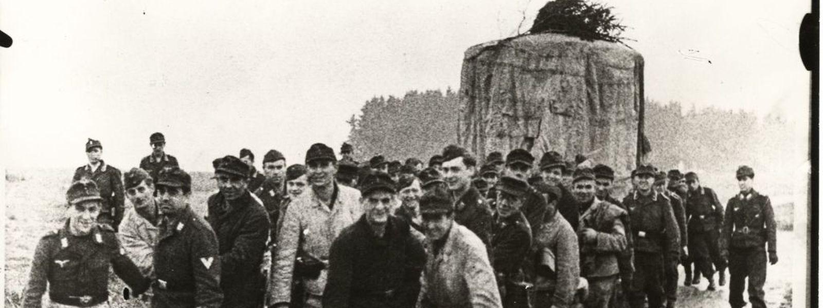 Wehrmachtssoldaten ziehen einen riesigen Scheinwerfer hinter sich her.