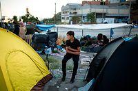 11.09.2020, Griechenland, Moria: Ein Kind sitzt am Rande einer Straße in der Nähe des ausgebrannten Flüchtlingslagers Moria. Mehrere Brände haben das Lager fast vollständig zerstört. Laut griechischer Regierung haben Migranten den Brand gelegt. Das Lager ist eigentlich auf 2800 Bewohner ausgelegt, zuletzt lebten dort aber mehr als 12 000 Migranten. Foto: Socrates Baltagiannis/dpa +++ dpa-Bildfunk +++