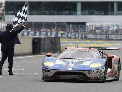 Germany's Dirk Mueller crosses the finish line on his Ford GT n�68, to win the LMGTE PRO category of the 84th Le Mans 24-hours endurance race, on June 19, 2016 in Le Mans, western France. Porsche snatched their 18th Le Mans 24 Hour Race victory with the Porsche 919 Hybrid N�2 in the most dramatic of circumstances after Toyota suffered engine failure with just three minutes left on June 19, 2016. / AFP PHOTO / JEAN-SEBASTIEN EVRARD