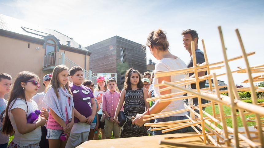 """Beim grenzübergreifenden Projekt """"L'atelier du géant"""" arbeiten Luxemburger und französische Teilnehmer an einer 7, 50 Meter hochen Marionette."""