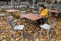 A young man eats his lunch at the patio of a closed restaurant in Vienna, Austria, on November 17, 2020. - Austria has entered its second lockdown with the new anti-coronavirus restrictions, shutting schools and shops until December 6, 2020 to get spiraling numbers of infections under control and urging Austrians to avoid all social contacts. (Photo by JOE KLAMAR / AFP)