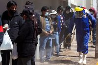A health worker sprays disinfectant against the spread of Covid-19 in the streets of the Andean city of Puno, Peru, close to the border with Bolivia, on April 19, 2021. - Peru registered this Sunday for the first time more than 400 deaths from covid-19 in 24 hours, amid a sharp increase in infections driven by the Brazilian variant of the virus spread throughout the country, reported the Ministry of Health. (Photo by Juan Carlos CISNEROS / AFP)