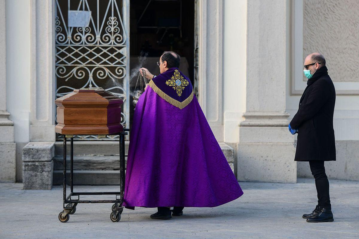 Ein Trauernder steht mit gebührendem Abstand zum Priester am Sarg seiner Mutter, die auf dem für die Öffentlichkeit geschlossenen Friedhof von Seriate nahe des nordtitalienischen Bergamo bestattet wird. Um das Virus einzudämmen, dürfen nur noch engste Angehörige bei der Bestattung anwesend sei.
