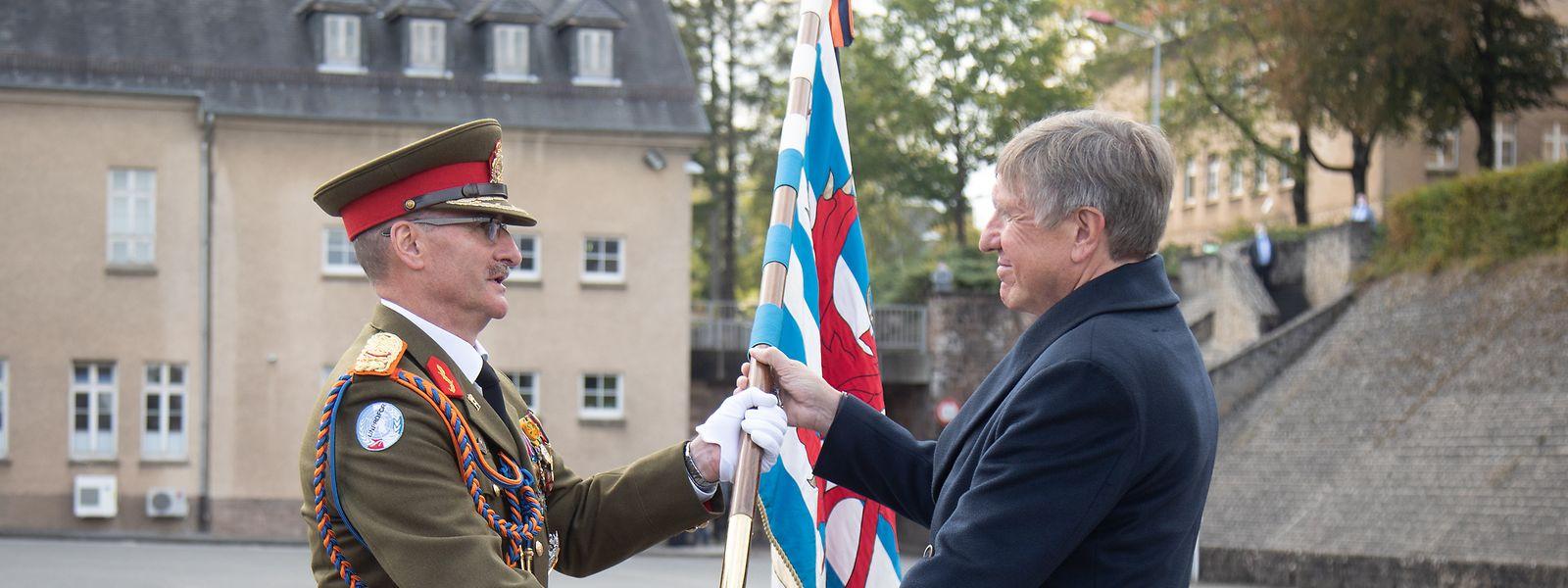 General Alain Duschène (links) gibt mit der Fahne symbolisch die Verantwortung über die Truppen bei Verteidigungsminister François Bausch ab.