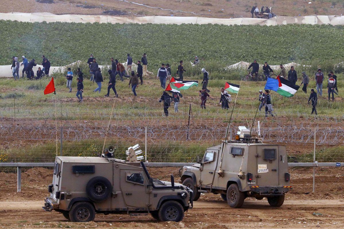 Israelische Militärfahrzeuge an der Grenze zu Gaza. Auf der anderen Seite demonstrieren Palästinenser.