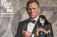 Vor einem Werbeplakat für den neuen Film in Bangkok schützt sich eine Frau mit einem Mundschutz.