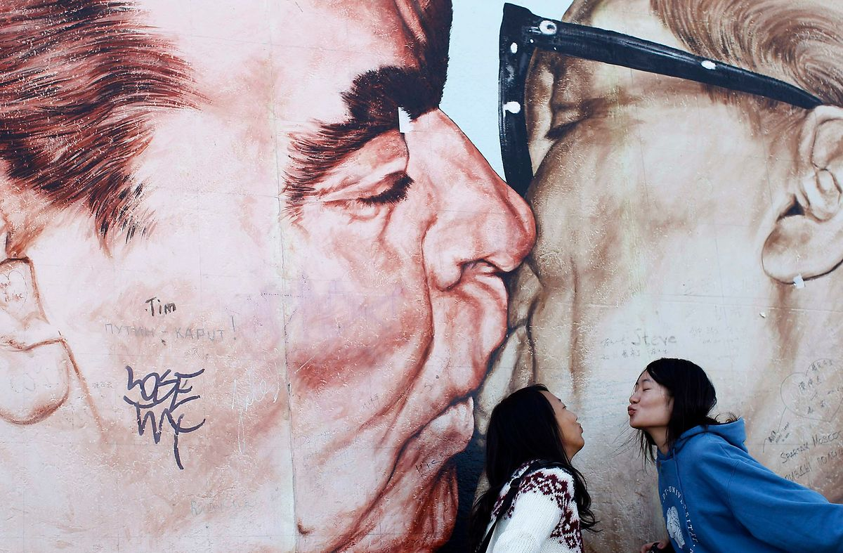 Chinese women kiss in front of a painting on the Berlin Wall depicting Erich Honecker and Leonid Brezhnev (L) in Berlin October 3, 2012. Wednesday marks the 22nd anniversary of German reunification, after decades of division into Soviet-controlled communist German Democratic Republic (GDR) in the east and the Federal Republic of Germany in the west. REUTERS/Lisi Niesner (GERMANY - Tags: POLITICS ANNIVERSARY)