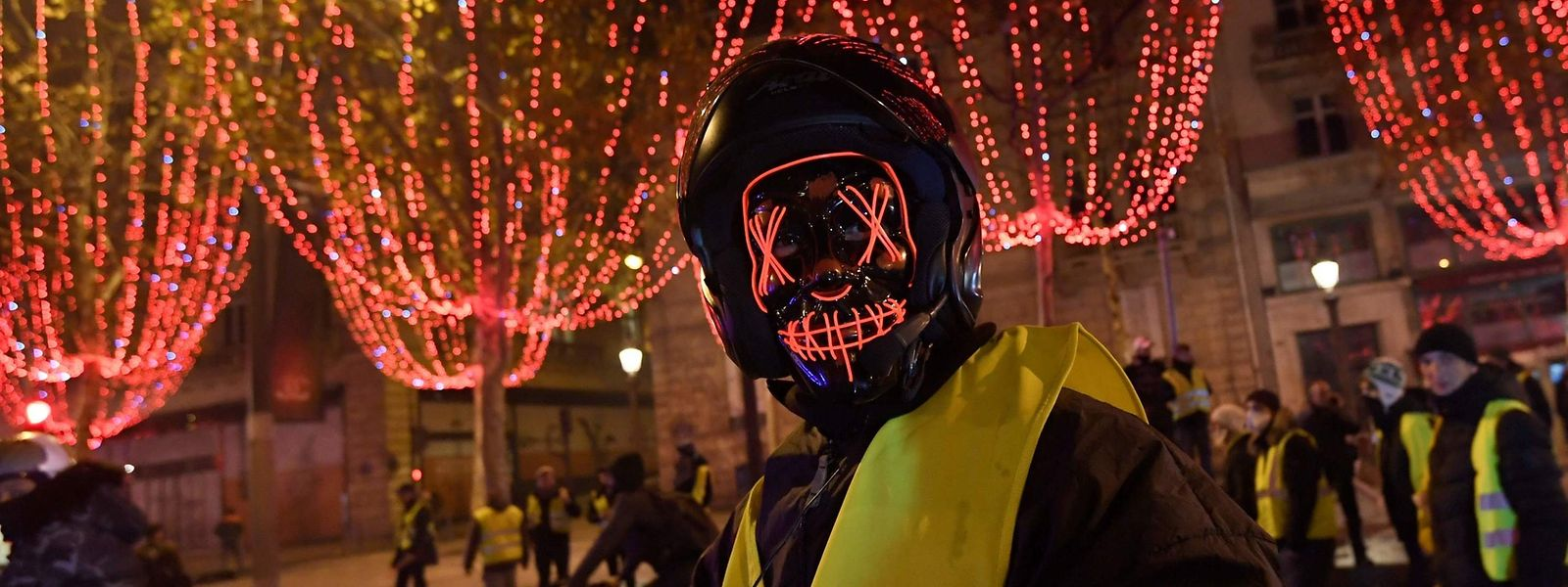 Les illuminations de Noël des Champs-Elysées se reflètent sur la visière du casque d'un manifestant en deux-roues: un effet digne d'un film de science-fiction.