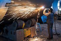 ARCHIV - 17.11.2015, Brandenburg, Fürstenwalde: In einer Firma wird an einem Stahlsegment für einen Windradturm gearbeitet. Trotz der Konjunktureintrübung und des Stellenabbaus bei einigen Konzernen machen sich Wirtschaftsexperten vorerst keine großen Sorge um den Arbeitsmarkt. Foto: Patrick Pleul/zb/dpa +++ dpa-Bildfunk +++