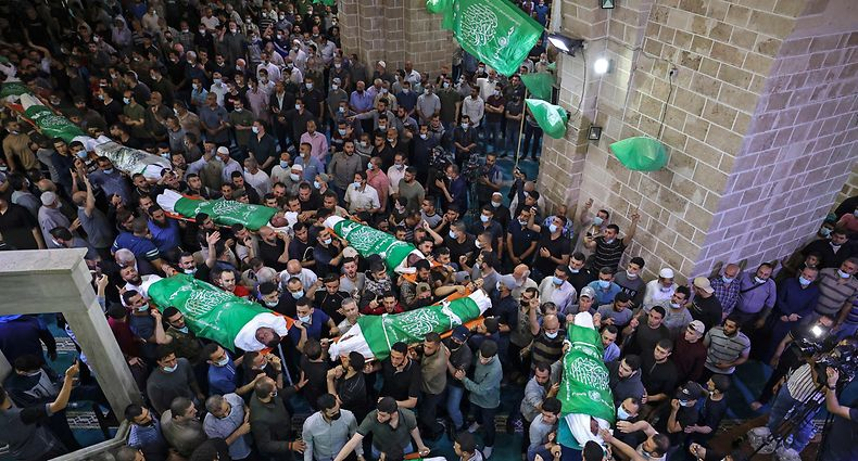 TOPSHOT - Palestinians carry the bodies of 13 Hamas militants, killed in Israeli air strikes, during their funeral at the al-Omari mosque in Gaza City, on May 13, 2021. - Despite global alarm and diplomatic efforts to halt the spiralling violence, hundreds of rockets tore through the skies over the Gaza Strip overnight and Israel's air force launched multiple strikes with fighter jets, targeting what it described as locations linked to Hamas, the Islamist group that controls Gaza. (Photo by MAHMUD HAMS / AFP)