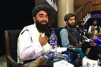 Taliban spokesperson Zabihullah Mujahid (L) attends the first press conference in Kabul on August 17, 2021, following their stunning takeover of Afghanistan. (Photo by Hoshang HASHIMI / AFP)