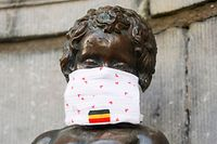 A picture shows the Manneken Pis wearing a mouth mask, in Brussels, on May 11, 2020 as Belgium goes into its ninth week of confinement due to the COVID-19 pandemic. (Photo by THIERRY ROGE / BELGA / AFP) / Belgium OUT